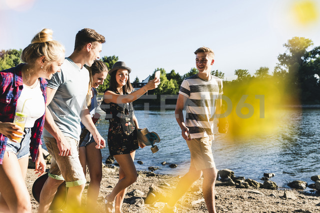 Group of happy friends walking at the riverside - UUF14877