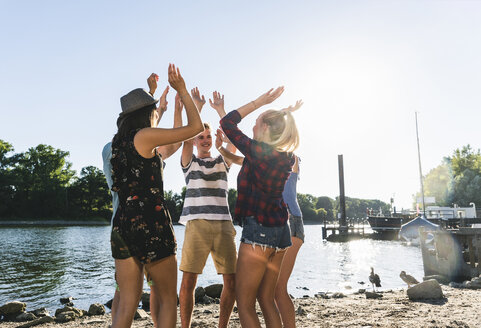 Group of friends raising their hands at the riverside - UUF14895