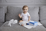 Baby boy with blond hair sitting on sofa, playing with tissue paper. - MINF04270