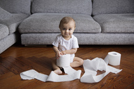 Baby boy with blond hair sitting on hardwood floor, playing with toilet paper rolls. - MINF04273