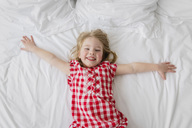 High angle view of smiling blond girl wearing red and white checked dress lying on bed. - MINF04303