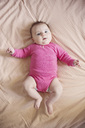 High angle view of baby girl wearing pink onesie lying on a bed. - MINF04330
