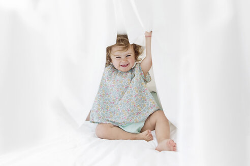 A young child, a girl in a floral dress liftin a sheet above her head, playing hiding - MINF04360