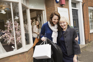 Two women with shopping bags hugging on the street outside a wedding dress shop - MINF04387