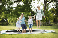 Man, woman, boy and girl holding hands, jumping on a trampoline set into the ground in a garden. - MINF04432