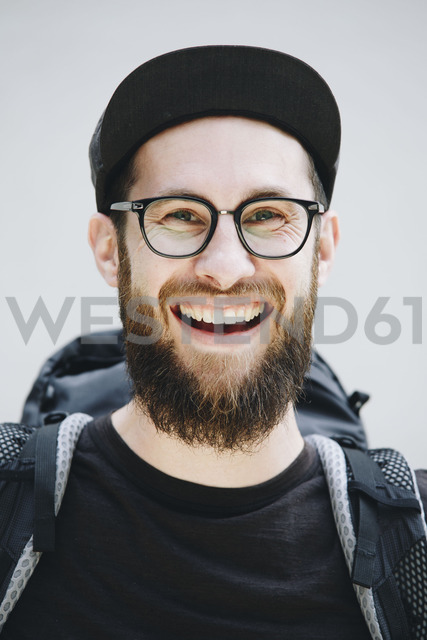 Portrait of laughing man with backpack dressed in black - NGF00464