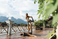 Laos, Vang Vieng, Young couple doing acro-yoga on a terrace - AFVF01217