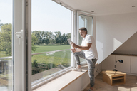 Mature man using tablet at the window in empty room - JOSF02443