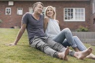 Smiling mature couple sitting in garden of their home - JOSF02449
