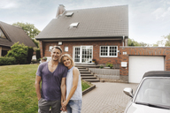 Portrait of smiling mature couple standing in front of their home - JOSF02455