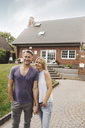 Portrait of smiling mature couple standing in front of their home - JOSF02458