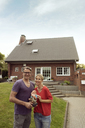 Portrait of smiling mature couple standing in front of their home holding garden gnome - JOSF02461