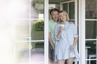 Smiling mature couple standing at French window - JOSF02464