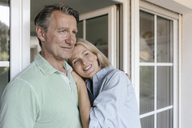 Portrait of smiling mature couple at French window - JOSF02470