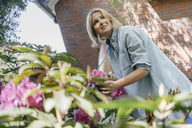Smiling mature woman with flowers in garden - JOSF02473