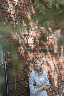 Relaxed mature woman leaning at house wall holding pruner - JOSF02476