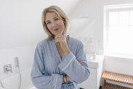 Portrait of smiling mature woman in bathroom - JOSF02482
