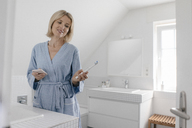 Smiling mature woman with cell phone and toothbrush in bathroom - JOSF02488