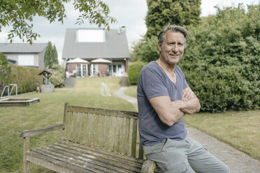 Portrait of smiling mature man in garden of his home - JOSF02500