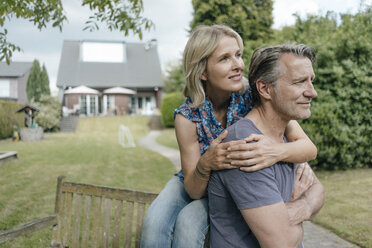 Smiling mature couple embracing in garden of their home - JOSF02503
