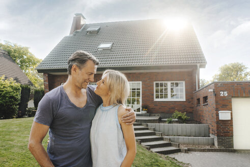 Smiling mature couple embracing in garden of their home - JOSF02506