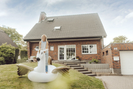 Portrait of smiling mature woman with inflatable pool toy in garden of her home - JOSF02512