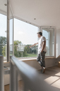 Mature man standing at the window in empty room - JOSF02515