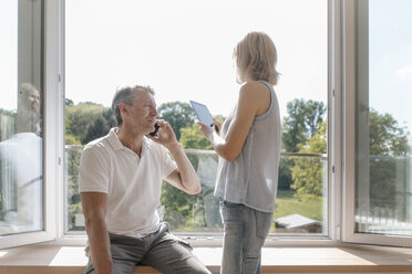 Mature couple with cell phone and tablet at the window - JOSF02518
