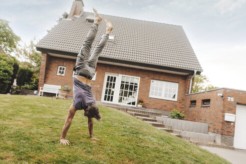 Mature man doing a handstand in garden of his home - JOSF02530