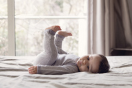 Side view of baby girl with brown hair wearing onesie lying on a bed, legs raised. - MINF04578