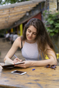 Young woman sitting at table taking notes - AFVF01227