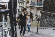 France, Paris, young couple walking in the district Montmartre - AFVF01242
