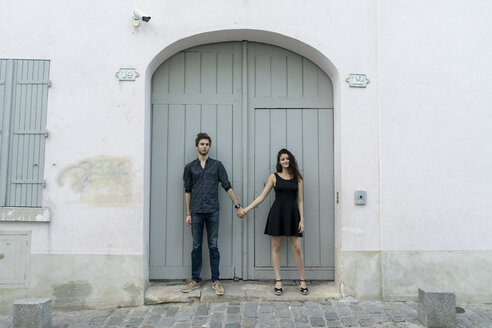 Young couple standing hand in hand in front of building - AFVF01260