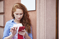Young woman using a cell phone during a work break - ABIF00803