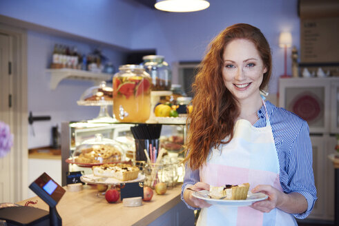 Portrait of smiling young woman serving cake in a cafe - ABIF00806
