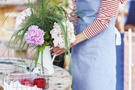 Woman decorating the table with flowers - ABIF00809
