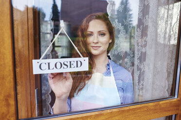 Portrait of young woman closing a shop - ABIF00812