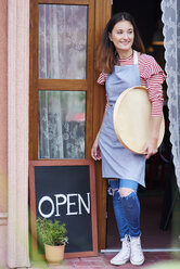Smiling woman standing at open door of acafe - ABIF00815
