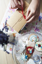 Woman tying a ribbon on a gift next to cakestand with cakes - ABIF00821