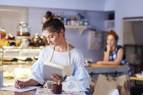 Woman working in a cafe taking notes - ABIF00827