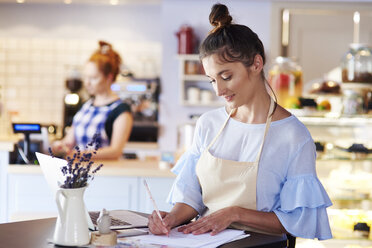 Woman working in a cafe taking notes - ABIF00830