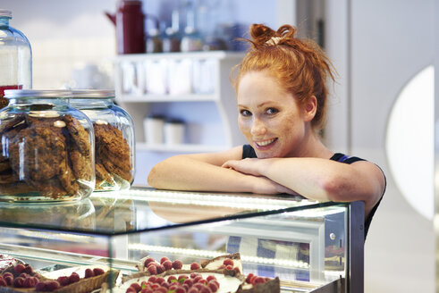 Portrait of smiling young woman at the cake display in a cafe - ABIF00833