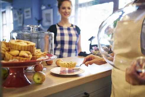 Woman working in a cafe serving a piece of cake - ABIF00839