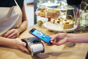 Customer paying cashless with smartphone in a cafe - ABIF00854