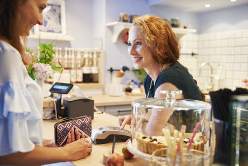Customer paying by credit card in a cafe - ABIF00857