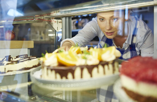 Woman working in a cafe serving a piece of cake - ABIF00866