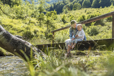 Mother and daughter sitting on wooden bridge, mountain stream - DIGF04726