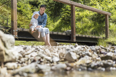 Mother and daughter sitting on wooden bridge, mountain stream - DIGF04729