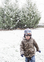 A child, a boy wearing a coat and standing in front of snowy trees. - MINF05007
