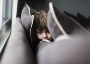 A child, boy hiding between the cushions of a sofa. - MINF05010